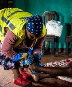 A community health care worker cleans an elderly woman during her visits around the community of Sweet Waters in KwaZulu-Natal. She resorts to using bread bags in the absence of gloves.