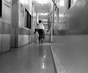 A nurse walks down a Gauteng hospital passage way with a child in this file photo.