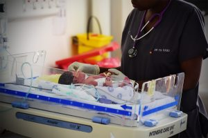 A nurse looking down at a neonate in a hospital ward.
