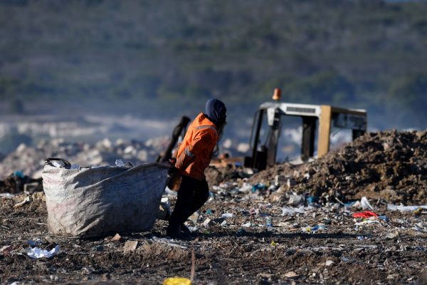 All in a day's work. A waste picker drags his stuffed bag through the landfill site. PHOTO: Black Star/Spotlight
