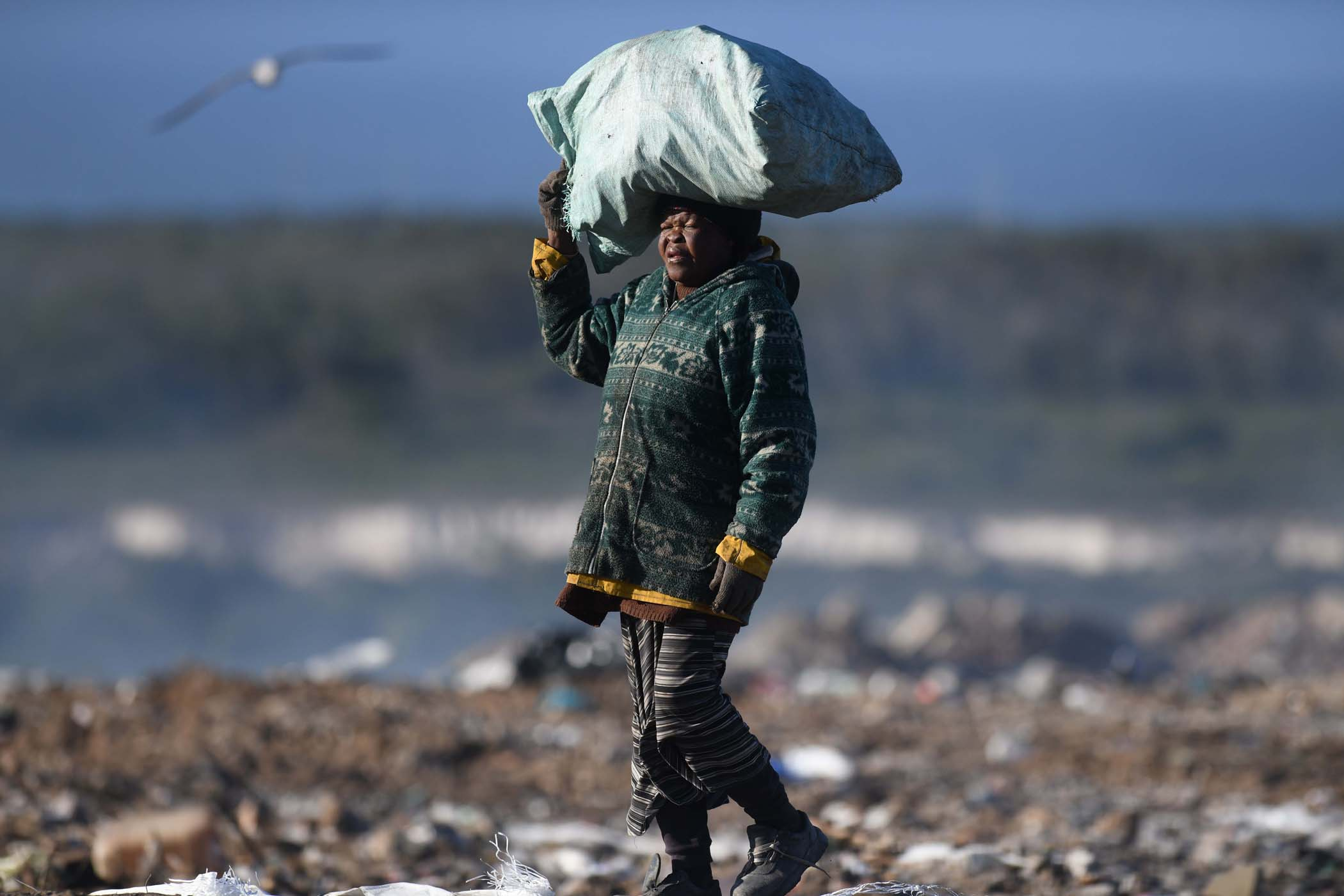 a woman carries her bag of recyclables on her head.