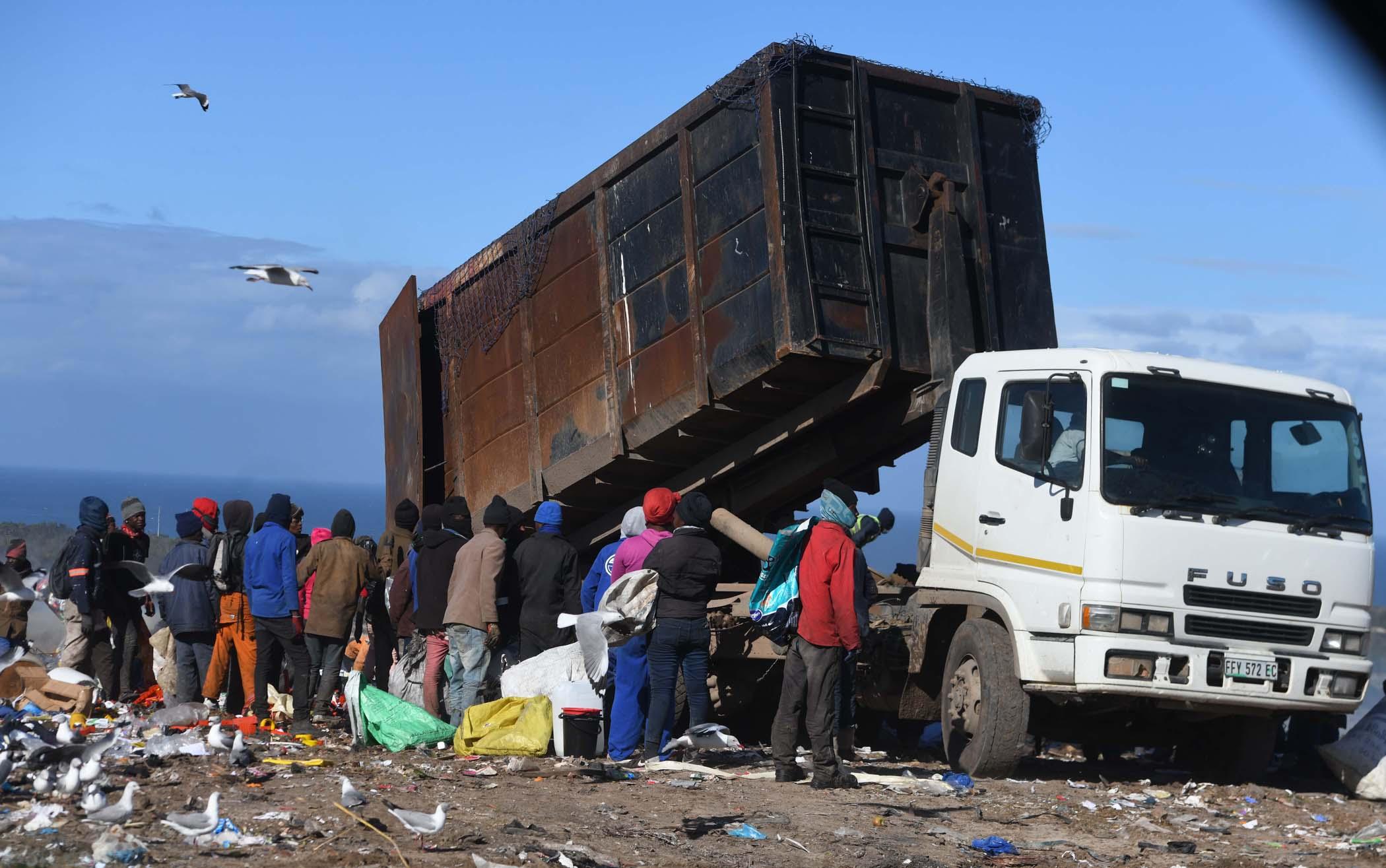 Waste pickers gather around a garbage disposal truck. Photo Black Star