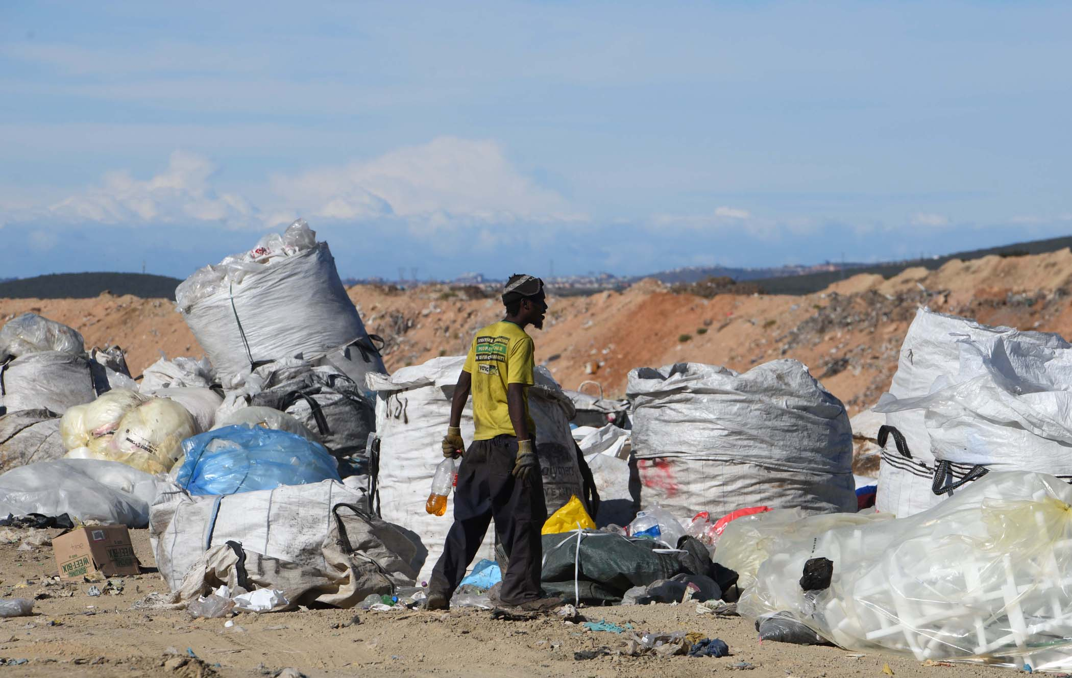 "A man dressed in a yellow ANC T-shirt with ""A better life for all"" written on it, stands guard over   massive bags of recyclables ready to be transported from the land fill site. PHOTO: Black Star/ Spotlight"