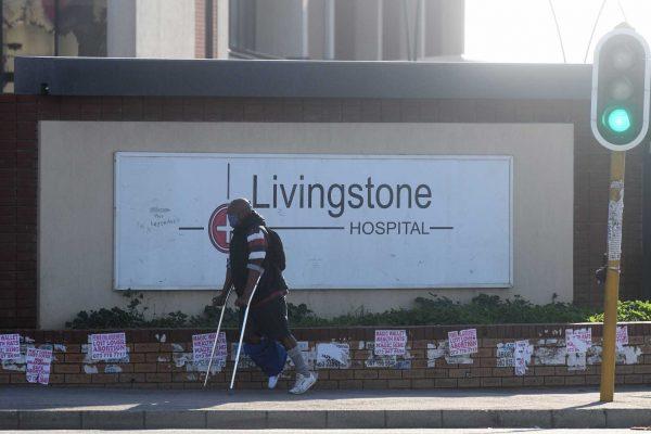man on crutches walking passed livingstone hospital