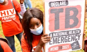 TAC member holding up TB poster calling for TB to be declared a national emergency.