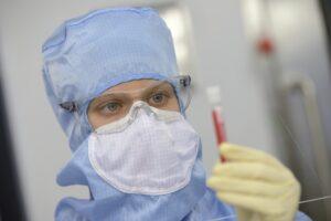 researcher holding a vial. PHOTO: Sanofi Pasteur/Patrick Boulen