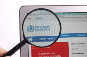 screen with WHO logo under magnifying glass. PHOTO: Jernej Furman