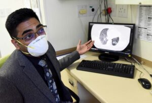 DR Rubeshan Perumal in front of his computer showing a lung.