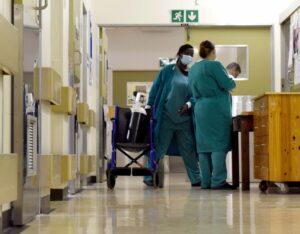 Hospital corrider with nurses at a nurses station.