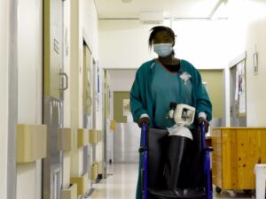 person pushing oxygen cylinder in the hospital corridor.