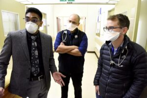 three doctors working at the post covid clinic at Groote Schuur discussing in the corridor.