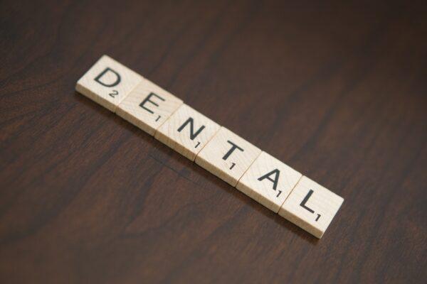 scrabble blocks spelling dental.