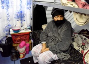 Elaine Neethling sits alone on her bed surrounded by some of her belongings at the Culemborg site.
