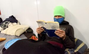 Michael Yel reading the bible, is homeless after he lost his job last year due to the pandemid.