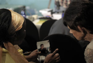 Family members at the arbitration hearings showing each other photos of their deceased loved ones. Joyrene Kramer