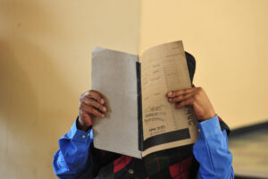 A patient with cataracts holding up his file close to his face to see better.
